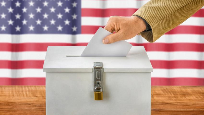 Mano colocando voto en una urna.