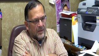 Erasmo Castro sentado frente a su escritorio.