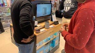 Clientes se interesan por un equipo de asistente inteligente por comando de voz desarrollado por Amazon a la venta en una tienda tecnológica en el centro de Nueva Delhi, India.