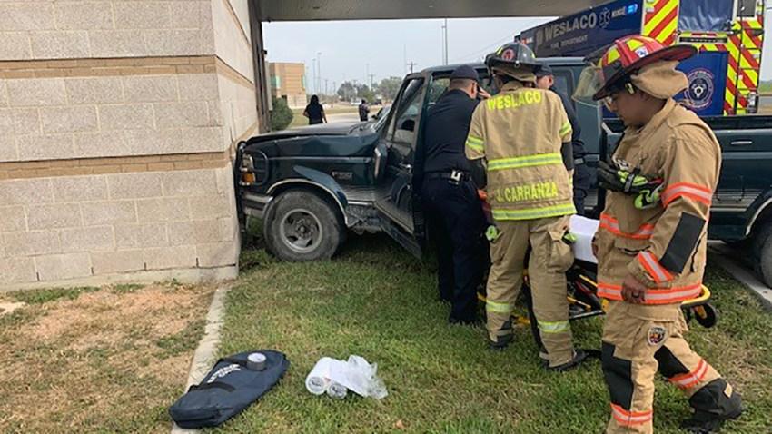 Bomberos y paramédicos auxiliando al conductor de una camioneta.