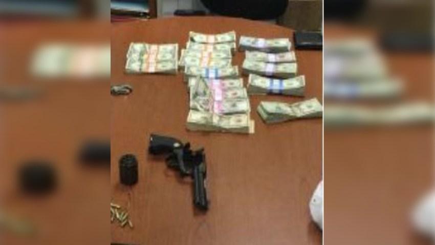 dinero en efecto y una pistola sobre una mesa.
