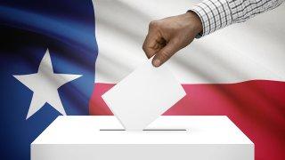 Mano colocando voto en una urna con la bandera de Texas en el fondo.
