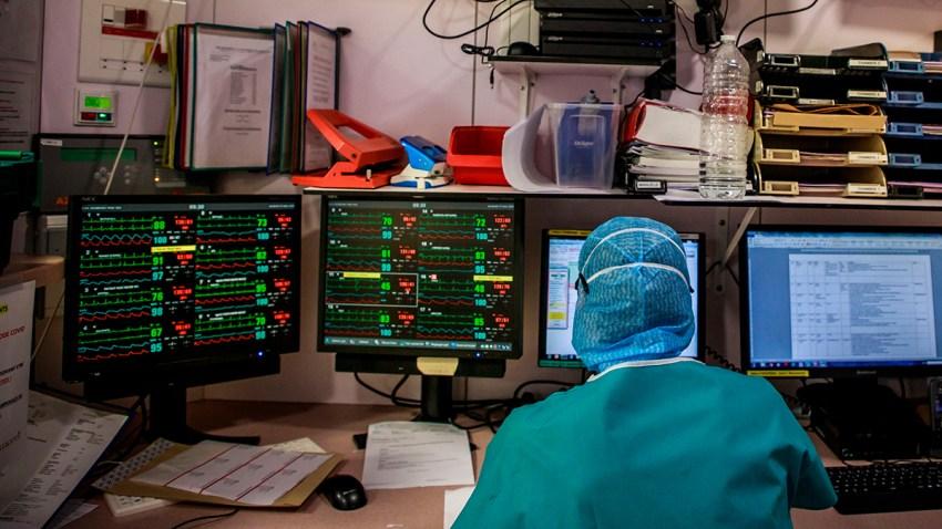 En la foto, un médico con vestuario protectivo sentado enfrente de pantallas.