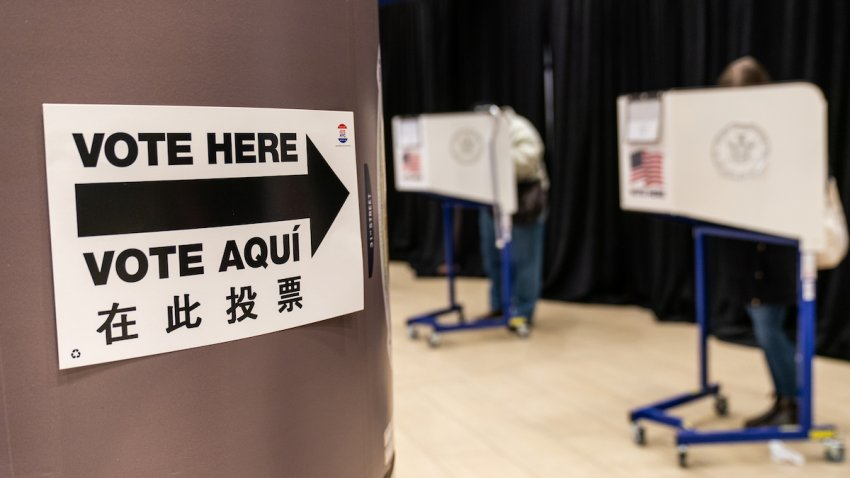 """A sign reads """"Voter Here"""" at an early voting polling location for the 2020 Presidential election"""