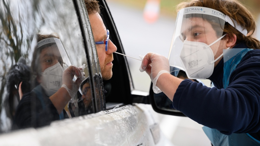 A member of staff is reflected in the car window as Nick Markham, the founder of ExpressTest, takes a PCR swab test at Gatwick Airport on November 27, 2020 in London