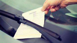 foto de una mano agarrando una multa.
