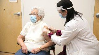 Farmacéutica administrando vacuna contra el coronavirus a una señora.