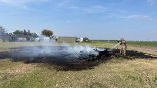 bombero echando agua a un incendio de maleza.