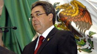 Fotografía de un hombre de mediana edad, con lentes y cabello entrecano, vestido con traje oscuro, camisa blanca y corbata color vino. El hombre está colocado de tres cuartos y era gobernador de Coahuila.