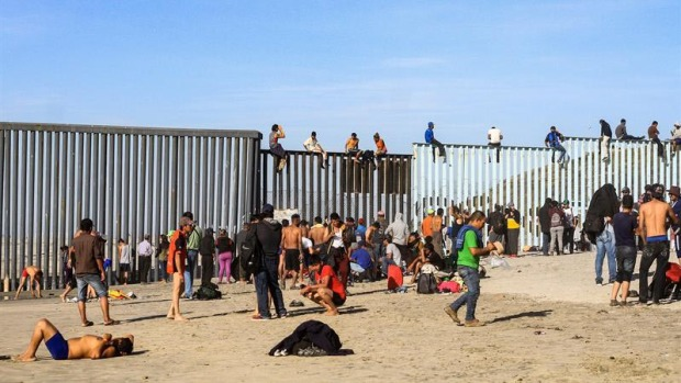 Migrantes trepan la valla que divide a México de EEUU