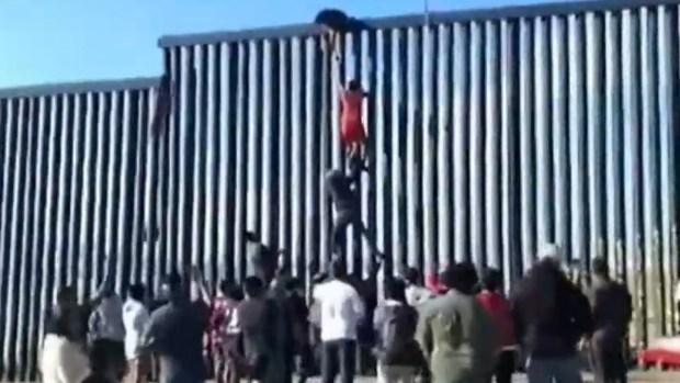 [TLMD - SD] En video: forman escalera humana para cruzar el muro